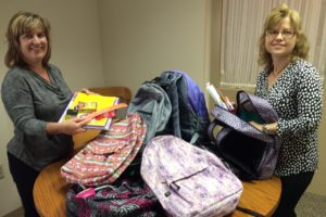 GKH paralegals Susan Miller and Jennifer Marcus with some of the 18 backpacks donated to LAPA.